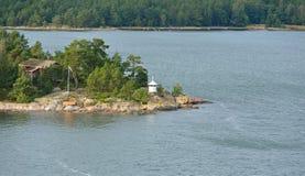 Zielona wyspa z czerwieni latarnią morską i domem Zdjęcia Royalty Free