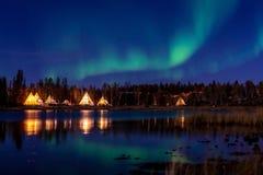 Zielonawy aurora borealis nad iluminującym Tipi blisko jeziora, Żółty nóż zdjęcia stock