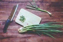 Zielone cebule z nożem na ciapanie desce na drewnianym Zdjęcia Stock