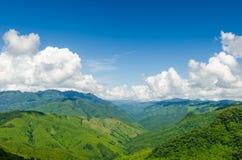 Zielone góry i niebieskie niebo z chmurami Zdjęcia Stock