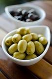 Zielone i czarne oliwki w ceramicznych garnkach Zdjęcie Stock