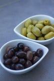 Zielone i czarne oliwki w ceramicznych garnkach Obraz Stock