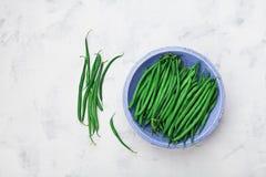 Zielone lub smyczkowe fasole w błękitnym nieociosanym pucharze na bielu kamienia stołowym odgórnym widoku Organicznie rolny jedze Obrazy Stock