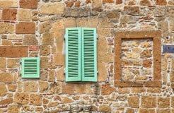 Zielone nadokienne żaluzje na stary kamień textured ścianie, Włochy Fotografia Stock