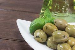 Zielone oliwki na z drewnianym biurkiem Zdjęcie Royalty Free