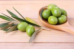 Zielone oliwki w drewnianej łyżce Obrazy Stock
