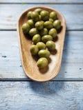 Zielone oliwki w drewnianym pucharze Zdjęcia Stock