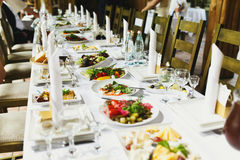 Zielone sałatki kłamają na białych talerzach na obiadowym stole Fotografia Stock
