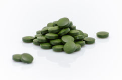Zielone spirulina chlorella gałęzatki pigułki zamykają up na bielu Zdjęcia Royalty Free