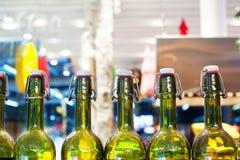 Zielone szklane butelki wino w linii na drewnianej półce, prętowy wewnętrzny projekt, wino degustacji pojęcie, życie nocne styl,  zdjęcia stock