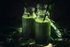 Zielonego detox szpinaków avocado jabłczany napój, smoothies w szklanej butelce, rocznika drewniany tło, depresja klucz, selekcyj zdjęcie stock