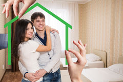 Zielonego domu kształt z młodą rodziną inside Fotografia Stock