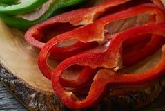 Zielonego i czerwonego pieprzu plasterki na tnącej desce Zdjęcia Stock