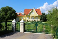 Zielonego metalu dokonany ogrodzenie z kamiennymi filarami przed nowożytnym podmiejskim rodzina domem z garażem obrazy royalty free