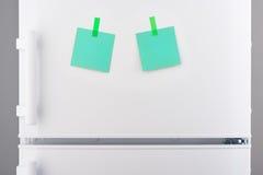 Zielonego papieru notatki dołączali z majcherami na białej chłodziarce Zdjęcie Stock
