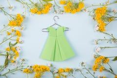 Zielonego papieru origami suknia na wieszaku otaczającym z żółtymi i białymi małymi kwiatami na światło mennicy tle Obraz Royalty Free