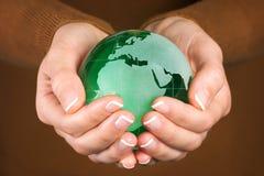 Zielonego szkła kula ziemska w ręce Fotografia Royalty Free