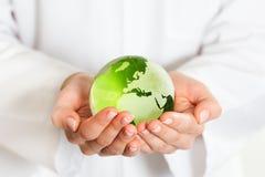 Zielonego szkła kula ziemska w ręce Zdjęcia Stock