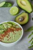 Zielonego szpinaka smoothy puchar nakrywający z ogórka, avocado i lna ziarnami na kamiennym tle, Obrazy Stock