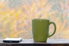Zielonej herbaty filiżanka na drewnianym windowsill obok telefonu gdy ja r obrazy stock
