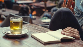 Zielonej herbaty i białej strony notatnik z kobiet rękami na drewnianym stole Zdjęcie Stock
