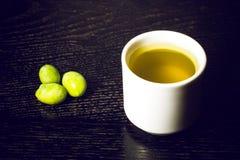 Zielonej oliwki jagody i nakrętka świeży oliwa z oliwek na czerni drewnianym Obrazy Royalty Free
