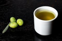 Zielonej oliwki jagody i nakrętka świeży oliwa z oliwek na czerni drewnianym Zdjęcia Stock