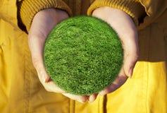 Zielonej trawy kula ziemska w rękach Zdjęcie Stock