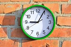Zielony ściennego zegaru obwieszenie na ściana z cegieł Fotografia Royalty Free