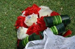 """Zielony ślubny bukiet z szkarłatnymi i białymi kwiatami na trawy Ñ """"nd biały koronkowy parasol Obrazy Stock"""