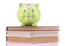 Zielony świniowaty moneybox i książki na białym odosobnionym tle Finanse, oszczędzania, pieniądze fotografia stock