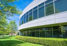 Zielony żywopłot i skoszony gazon wzdłuż round kształtnej ściany budynek biurowy zdjęcia stock