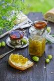 Zielony agrestowy dżem w słoju na drewnianym stole Zdjęcia Royalty Free