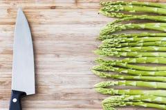 Zielony asparagus na drewnianej desce z kopia nożem i przestrzenią obrazy stock