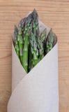 Zielony asparagus od rolnicy wprowadzać na rynek w brown papieru pakować - Fotografia Stock