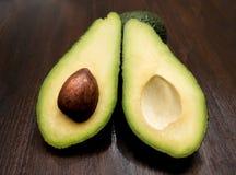 Zielony avocado ciie w przyrodnim lying on the beach na białym tle obrazy stock