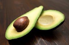 Zielony avocado ciie w przyrodnim lying on the beach na bia?ym tle obrazy stock