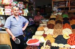 ZIELONY bazar ALMATY KAZACHSTAN, MAJ - 30, 2014 - Sprzedawca wysuszone owoc i dokrętki zdjęcie royalty free