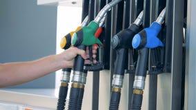 Zielony benzynowy nozzle dostaje stawiającym z powrotem w swój miejsce mężczyzną Benzyna, gaz, paliwo, ponaftowy pojęcie zbiory
