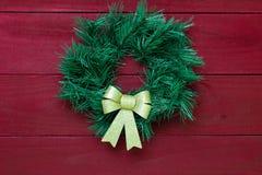 Zielony Bożenarodzeniowy wianek z złocistym łęku obwieszeniem na antykwarskim czerwonym drewnianym drzwi Fotografia Royalty Free