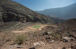 Zielony boisko piłkarskie po środku pustynnych gór Zdjęcia Royalty Free