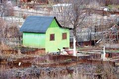 Zielony budynek dla życia, biedny zielony dom wśród żelaznego ogrodzenia i jesieni drzewa, Zdjęcie Stock