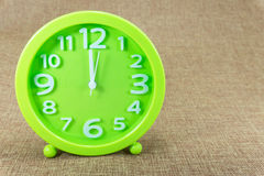 Zielony budzik na brown parciany tła przedstawienia 12:00 a M Obraz Royalty Free