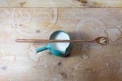Zielony ceramiczny pucharu miotacz ześrodkowywający na nieociosanym drewno stole owsa mleko, długa drewniana łyżka z owies głowam obraz royalty free