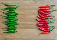 Zielony chili pieprz na lewej stronie i Czerwony chili pieprzu z prawej strony ciapanie bloku Zdjęcia Royalty Free