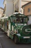 Zielony chodzący turysty pociąg na kołach jadących wzdłuż starego ulicznego pe Obraz Stock