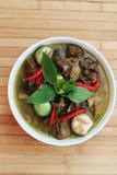 Zielony curry w białej filiżance na brown bambusowej podłoga Obrazy Royalty Free