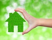 Zielony dom w ręce Obraz Royalty Free
