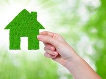 Zielony dom w ręce Obrazy Stock
