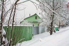 Zielony dom za greeny ogrodzeniem w śniegu Obraz Royalty Free